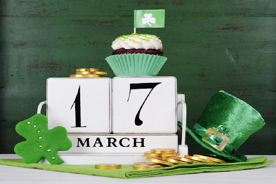 Happy St Patricks Day save the date white vintage wood calendar with cupcakes on vintage style green wood background.