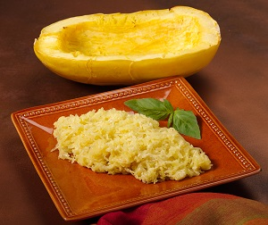Half of a cooked spaghetti squash and a plate of Spaghetti Squash Parmigiano