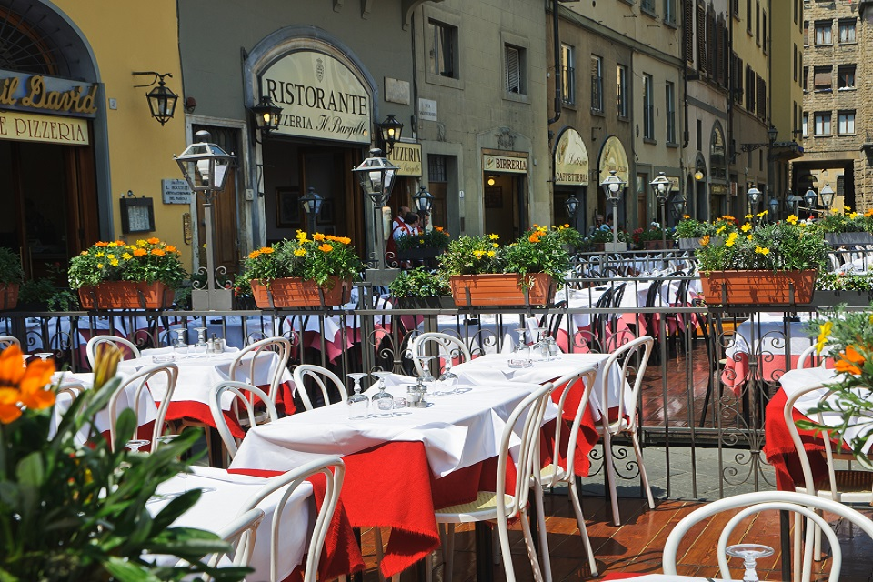 Red vested waiters await diners just before noon at one of the many alfresco dining choices that are offered on     the  Piazza della Signoria, Florence, Italy