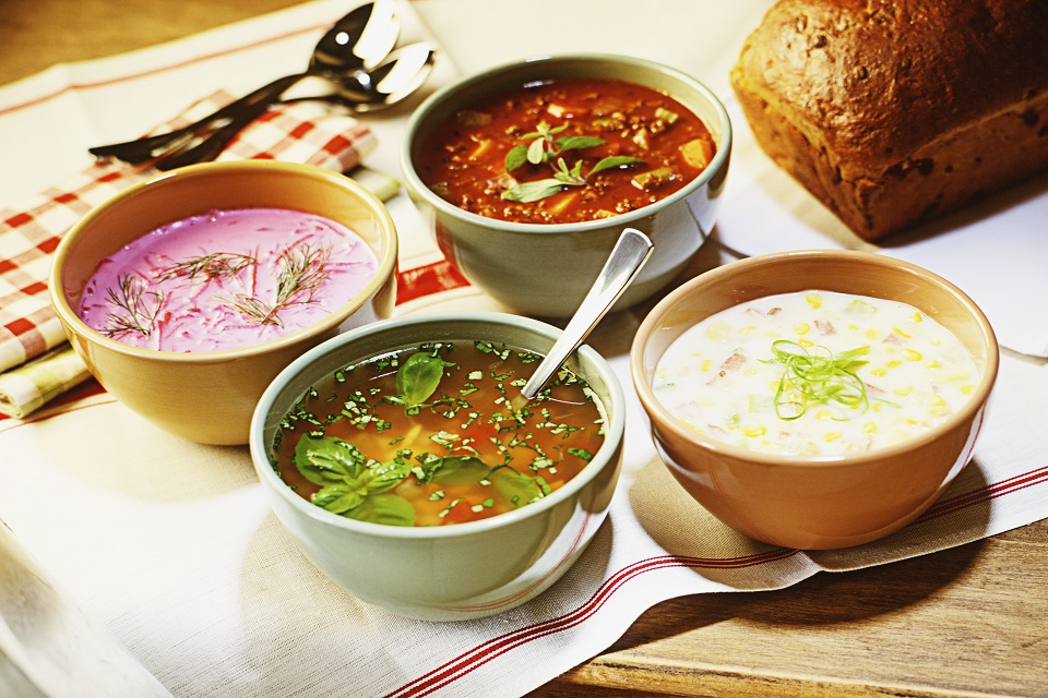 Assortment of soups, on a rustic country table setting.