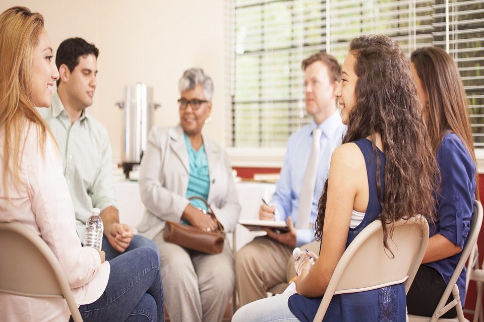 Multi-ethnic group of people in a group counseling session with a therapist.  The male counselor, psychiatrist, or therapist is taking notes on his notepad.  The rest of the group is talking, sharing together in an office setting.