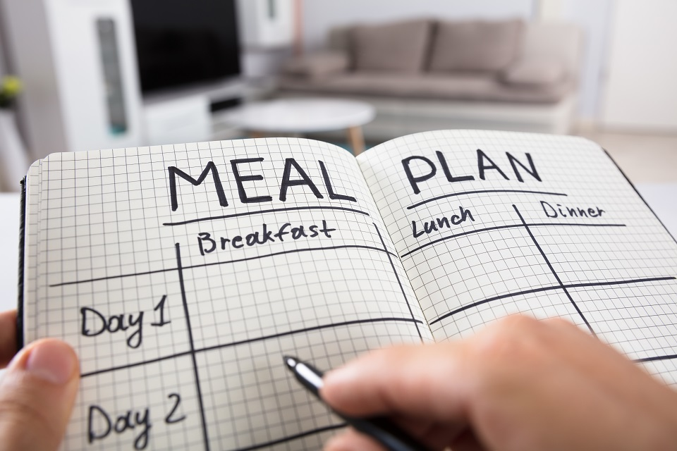 hand holding pen filling out meal plan in a notebook