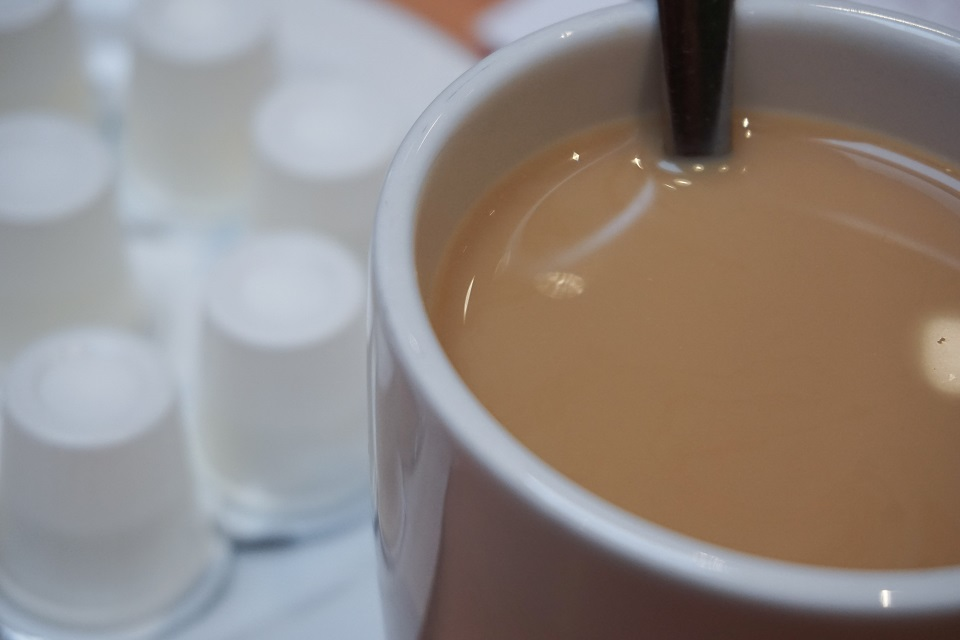 Cup of coffee with cream and individual creamers in background