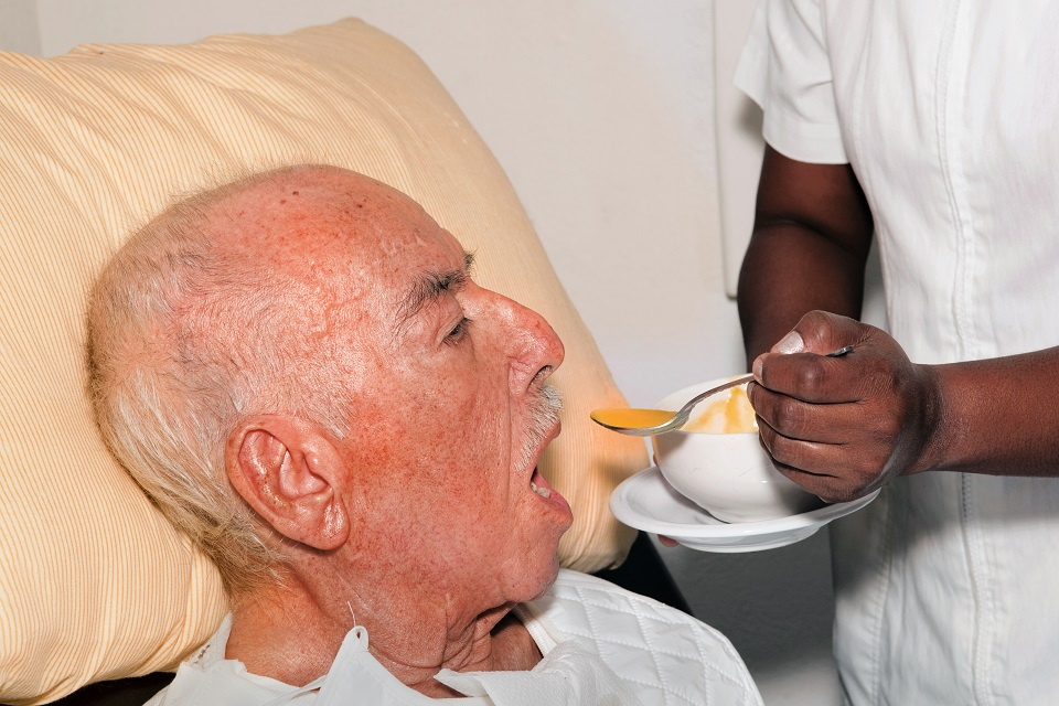 senior male 92 years old being fed by a nurse