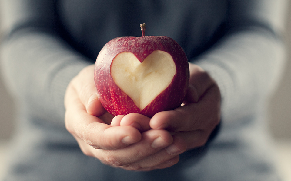 Hands holding an apple with heart shape carved into it.