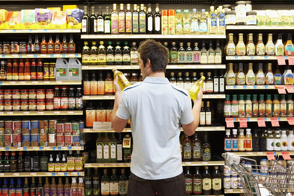 Man in grocery store looking at bottles of cooking oil