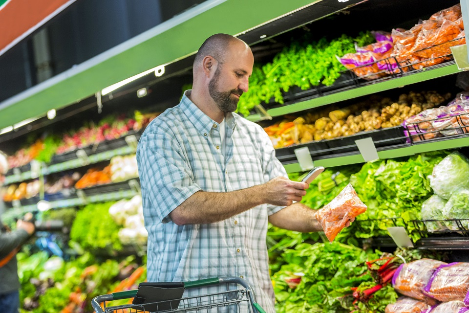 Man uses phone at grocery store to get more information about his purchases.