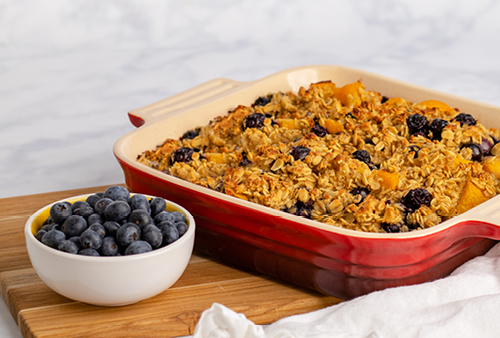 Baked Blueberry-Peach Oatmeal in baking dish with a bowl of fresh blueberries