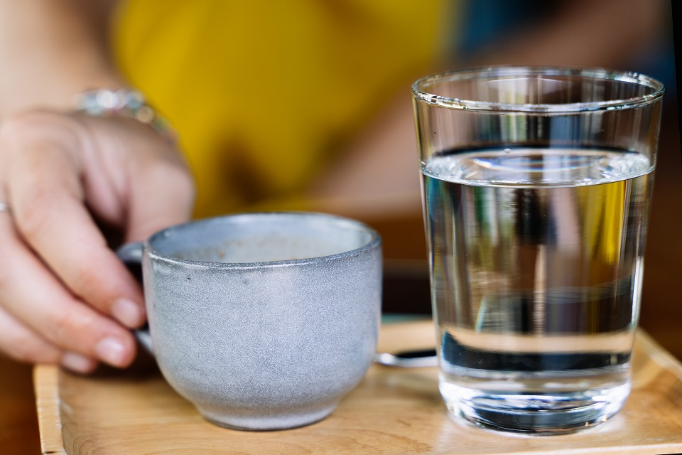 Hand holding a cup of coffee served with a glass of water and a spoon on a wooden plate on a wooden table