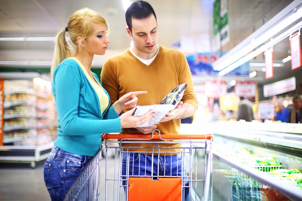 Early 30's couple buying frozen food in local supermarket.They are standing next to freezer section and reading labels and price tags, while she's still uncertain of which product to pick. Both casually dressed in green and brown sweaters.