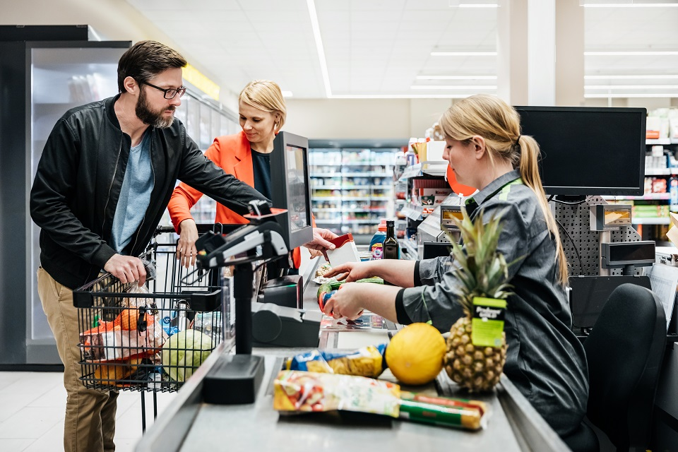 Mature Couple Putting Groceries On Conveyor At Checkout