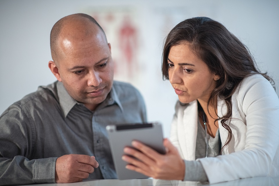 Female Dietitian Shares Information with Patient Using Digital Tablet