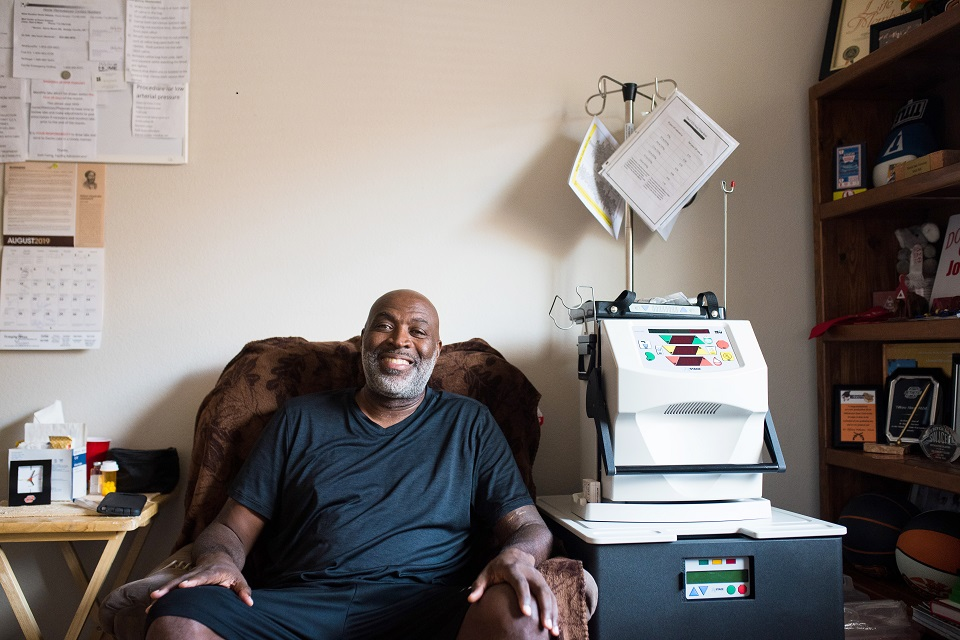 A man setting in a chair beside home hemodialysis machine.